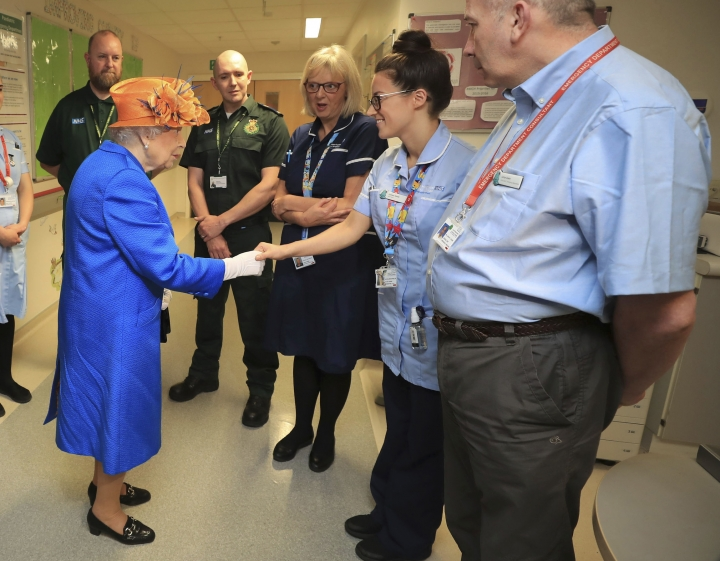 Britain's Queen Elizabeth II, centre, speaks with hospital personnel as she visits the Royal Manchester Children's Hospital to meet victims of the terror attack in the city earlier this week and to thank members of staff who treated them Thursday May 25, 2017. (Peter Byrne/Pool via AP)