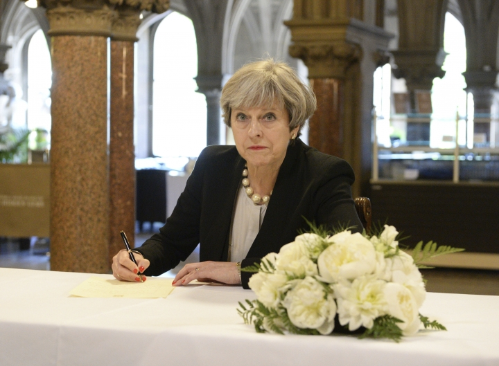 Britain's Prime Minister, Theresa May, writes a message at Manchester Town Hall in Manchester, England, Tuesday May 23, 2017, after a 23-year-old man was arrested in connection with Monday's Manchester concert bomb attack. The attack killed more than 20 people, including children, and injured dozens more. (Ben Birchall/Pool via AP)
