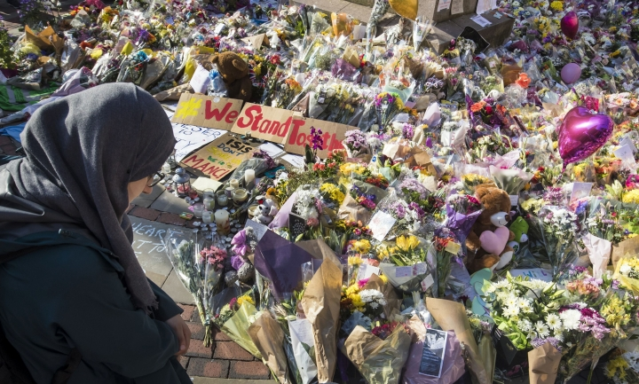 A woman looks at the floral tributes and messages left for the victims of the concert blast, during a vigil at St Ann's Square in central Manchester, England, Wednesday, May 24, 2017. British police say officers investigating the Manchester Arena concert blast have arrested a fifth suspect, and are assessing a package the suspect was carrying. Greater Manchester Police said the suspect was detained in Wigan, a town to the west of Manchester. (Danny Lawson/PA via AP)