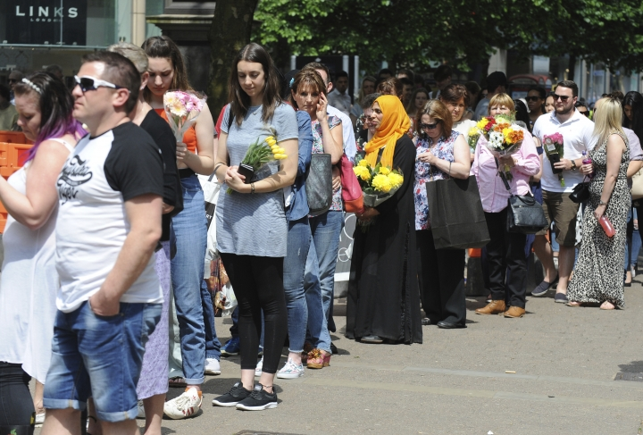 People queue to place flowers at St Ann's square in central Manchester, England Thursday May 25 2017. More than 20 people were killed in an explosion following a Ariana Grande concert at the venue late Monday evening. Britons will find armed troops at vital locations Wednesday after the official threat level was raised to its highest point. (AP Photo/Rui Vieira)