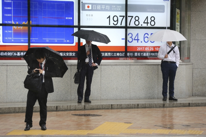 People stand in front of an electronic stock board of a securities firm in Tokyo, Friday, May 26, 2017. Asian stock markets are mixed Friday as investors weighed Wall Street's latest gains on strong earnings reports against the latest oil production cut that dragged down crude prices and commodity shares. (AP Photo/Koji Sasahara)