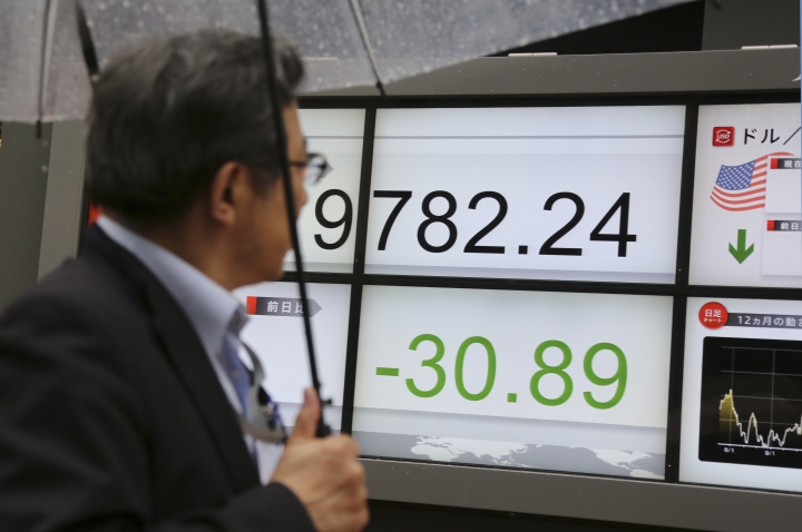 A man looks at an electronic stock board of a securities firm in Tokyo, Friday, May 26, 2017. Asian stock markets are mixed Friday as investors weighed Wall Street's latest gains on strong earnings reports against the latest oil production cut that dragged down crude prices and commodity shares. (AP Photo/Koji Sasahara)