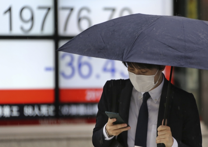 A man looks at his smartphone at an electronic stock board of a securities firm in Tokyo, Friday, May 26, 2017. Asian stock markets are mixed Friday as investors weighed Wall Street's latest gains on strong earnings reports against the latest oil production cut that dragged down crude prices and commodity shares. (AP Photo/Koji Sasahara)