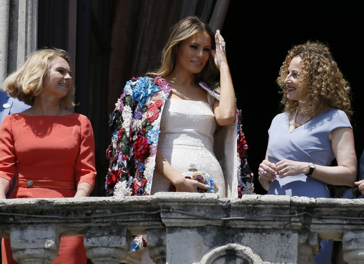 US First Lady Melania Trump, center, adjusts her hair as she stands with spouse of European Council President Donald Tusk Malgorzata Tusk, left, and Amanda Succi, partner of the mayor of Catania Enzo Bianco, on the balcony of Chierici Palace, part of a visit of the G7 first ladies in Catania, Italy, Friday, May 26, 2017. On Friday and Saturday, for the first time all seven are around the same table, including also newcomers Emmanuel Macron of France, Theresa May of Britain and the Italian host, Paolo Gentiloni, forging a new dynamic after a year of global political turmoil amid a rise in nationalism. (AP Photo/Domenico Stinellis)
