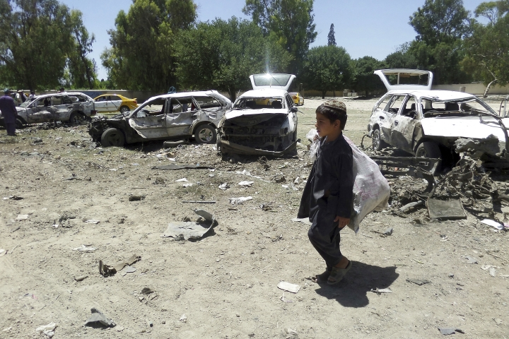 A boy walks passed damaged vehicles at the site of a suicide attack in eastern Khost province, Afghanistan, Saturday, May 27, 2017. At least 18 people, mostly civilians, were killed Saturday when a suicide car bomber targeted a convoy of provincial security forces in eastern Afghanistan, an Interior Ministry official said. (AP Photos/Nishanuddin Khan)