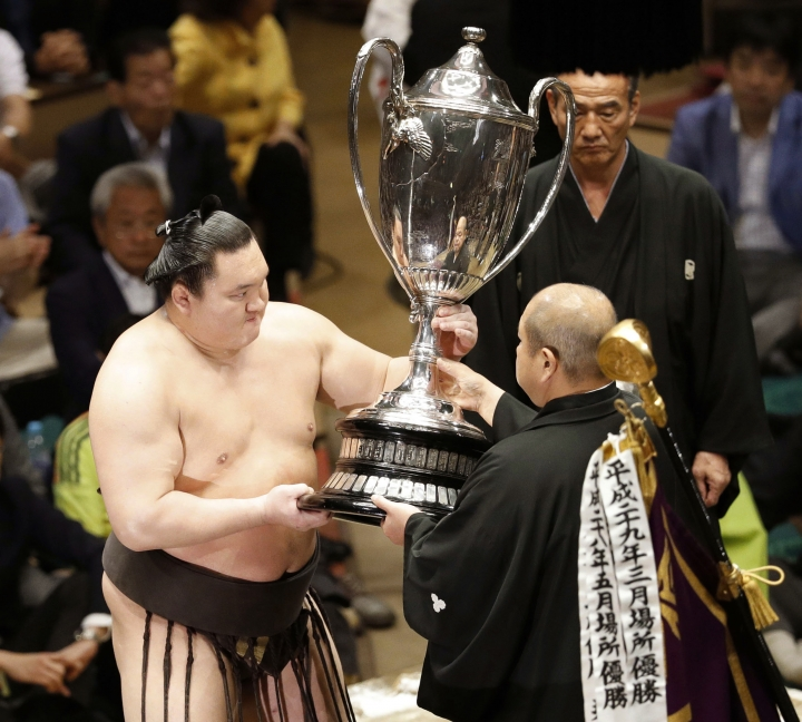 Grand champion Hakuho, left, receives the Emperor's Cup from Japan Sumo Association Chairman Hakkaku after winning the Summer Grand Sumo Tournament at Ryogoku Kokugikan in Tokyo Sunday, May 28, 2017. Hakuho forced out his compatriot Mongolian Harumafuji (11-4) in the day's final bout to improve to 15-0 a day after securing his first title in a year with a win over ozeki Terunofuji. Hakuho won the summer tourney last year but has struggled with foot and thigh injuries since then and missed much of the March tournament due to injury. (Yusuke Ogata/Kyodo News via AP)