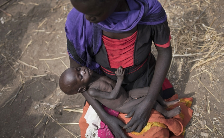 FILE - This is a Wednesday, April 5, 2017, file photo of Adel Bol, 20, cradles as she her 10-month-old daughter Akir Mayen at a food distribution site in Malualkuel in the Northern Bahr el Ghazal region of South Sudan. The head of the U.N.'s food and agriculture agency warned Tuesday May 30, 2017 that conflict in South Sudan could undermine hopes of avoiding a new famine next year. (AP Photo/File)