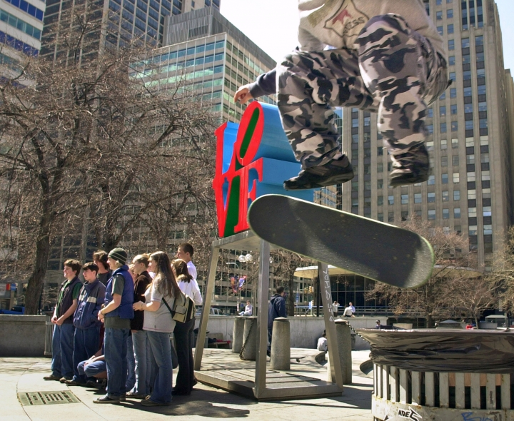 FILE – In this April 1, 2002, file photo, Mike Cole, of Jenkintown, Pa., right, performs a kick-flip over a trash can with his skateboard as tourists pose for photos in front of artist Robert Indiana's sculpture in John F. Kennedy Plaza, also known as Love Park, in Philadelphia. Granite slabs from Philadelphia's famed Love Park, a skateboarding mecca though for a long stretch an illegal one, are being shipped in 2017 to the city of Malmo, Sweden, nearly 4,000 miles away, for use in construction of a skate park there. (AP Photo/Douglas Bovitt, File)