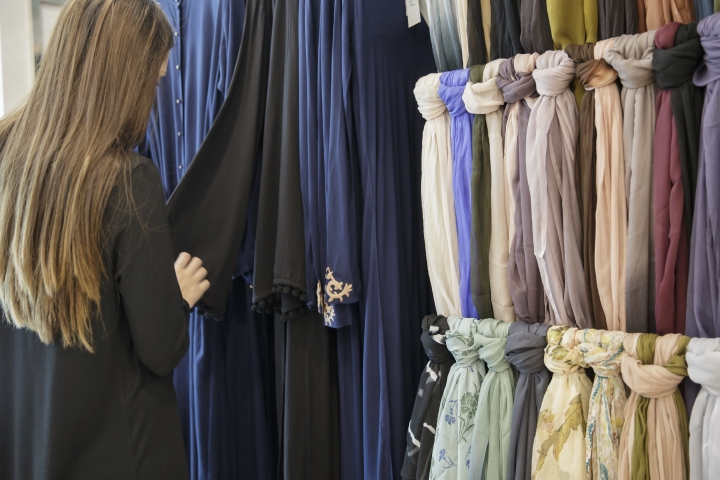 "A member of staff poses for a picture at the aab boutiq store at Upton Park, in London, Monday May 22, 2017. ""Mainstream fashion is now talking about modest fashion as a thing. Ten years ago, if you were a brand coming from a religious background and tried to sell it in department stores, calling it a modest or Muslim brand would be a kiss of death,"" said Reina Lewis, a professor at the London College of Fashion who has written two books about the topic. While the majority of those interested in covered-up fashion are young, cosmopolitan Muslim women, ""the term 'modesty' emerged in the niche market as a useful one because it's not faith-specific,"" Lewis added. (AP Photo/Tim Ireland)"