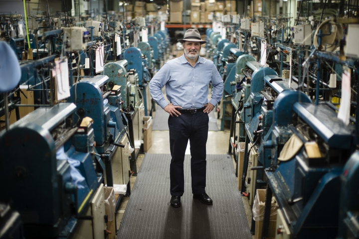 """Don Rongione, President and Chief Operating Officer of Bollman Hat Company poses for a photograph with knitting machine used in the manufacturing of Kangol hats the Bollman Hat Company in Adamstown, Pa., Monday, May 1, 2017. When the famous hat brand moved into the Pennsylvania factory last year from China, executives with the Bollman Hat Co. billed it as an effort to create U.S. manufacturing jobs. """"It has been certainly a bigger challenge than what we could've ever dreamed,"""" said Rongione. (AP Photo/Matt Rourke)"""