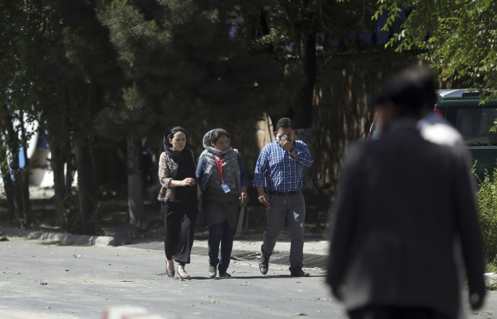 Roshan mobile company employees, walk away near the site of a suicide attack in Kabul, Afghanistan, Wednesday, May 31, 2017. A massive explosion rocked a highly secure diplomatic area of Kabul on Wednesday morning, causing casualties and sending a huge plume of smoke over the Afghan capital. (AP Photos/Massoud Hossaini)