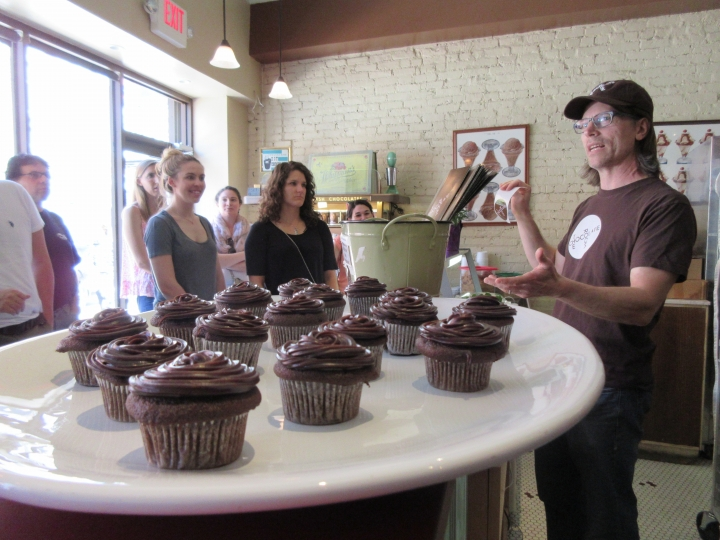 This April 28, 2017 photo shows Jon Payson, owner of The Chocolate Room in Brooklyn, N.Y., explaining how he and his wife started the business in a chat with a group on A Slice of Brooklyn's chocolate tour. The Chocolate Room is one of a number of stops on the tour. In addition to chocolate samples to taste, the tour offers a peek at the chocolate-making process and neighborhood visits. (AP Photo/Beth J. Harpaz)