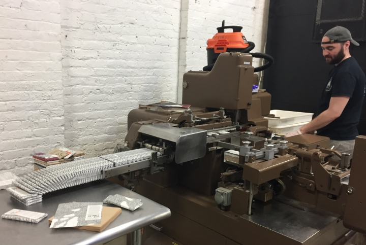 This April 28, 2017 photo shows William Widmaier operating a machine that wraps chocolate bars at Raaka Chocolate in the Red Hook section of Brooklyn, N.Y. Raaka is one of a number of stops on A Slice of Brooklyn chocolate tour, which offers chocolate samples to taste along with visits to different neighborhoods and insights into how some of the businesses on the tour got started. (AP Photo/Beth J. Harpaz)