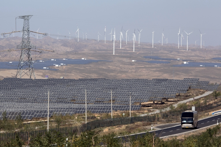 FILE - In this file photo taken Saturday, Oct. 10, 2015, a bus moves past by solar power and wind power farms in northwestern China's Ningxia Hui autonomous region. By backing off the U.S. commitment to address climate change, President Donald Trump leaves an opening for a chief economic rival, China, to expand its increasing dominance in the renewable energy industry. In reacting to Trump's announcement that he was withdrawing the U.S. from the Paris climate accord, China reaffirmed its commitment to the landmark agreement and is poised to spend heavily in coming years on renewables. (AP Photo/Ng Han Guan, File)