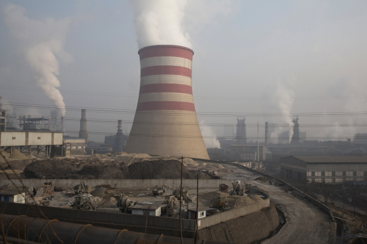 FILE - In this file photo taken Dec. 30, 2016, smoke and steam spew from the sprawling complex that is a part of the Jiujiang steel and rolling mills in Qianan in northern China's Hebei province. By backing off the U.S. commitment to address climate change, President Donald Trump leaves an opening for a chief economic rival, China, to expand its increasing dominance in the renewable energy industry. In reacting to Trump's announcement that he was withdrawing the U.S. from the Paris climate accord, China reaffirmed its commitment to the landmark agreement and is poised to spend heavily in coming years on renewables. (AP Photo/Ng Han Guan, File)