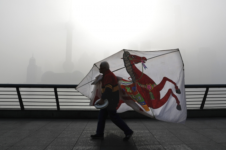 FILE - In this file photo taken Thursday, April 14, 2016, a Chinese man carries his kite past the Pudong Financial District shrouded with fog and pollution at the Shanghai Bund in Shanghai, China. By backing off the U.S. commitment to address climate change, President Donald Trump leaves an opening for a chief economic rival, China, to expand its increasing dominance in the renewable energy industry. In reacting to Trump's announcement that he was withdrawing the U.S. from the Paris climate accord, China reaffirmed its commitment to the landmark agreement and is poised to spend heavily in coming years on renewables. (AP Photo/Andy Wong, File)