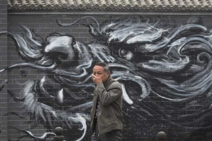 FILE - In this file photo taken Tuesday, Dec. 20, 2016, a Chinese man places his hand over his mouth as he walks past graffiti of a dragon during a day of heavy pollution in Beijing, China. By backing off the U.S. commitment to address climate change, President Donald Trump leaves an opening for a chief economic rival, China, to expand its increasing dominance in the renewable energy industry. (AP Photo/Ng Han Guan, File)