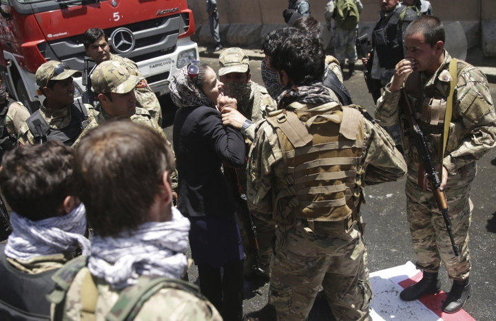 A woman tries to stop police from firing on protesters during a demonstration in Kabul, Afghanistan, Friday, June 2, 2017. Hundreds of demonstrators demanded better security in the Afghan capital in the wake of a powerful truck bomb attack that killed scores of people. (AP Photo/Massoud Hossaini)