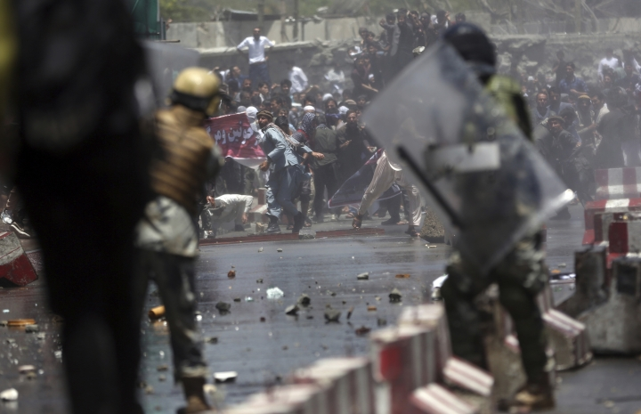 Protesters throw stones towards security forces during a demonstration in Kabul, Afghanistan, Friday, June 2, 2017. Hundreds of demonstrators demanded better security in the Afghan capital in the wake of a powerful truck bomb attack that killed scores of people. (AP Photos/Massoud Hossaini)