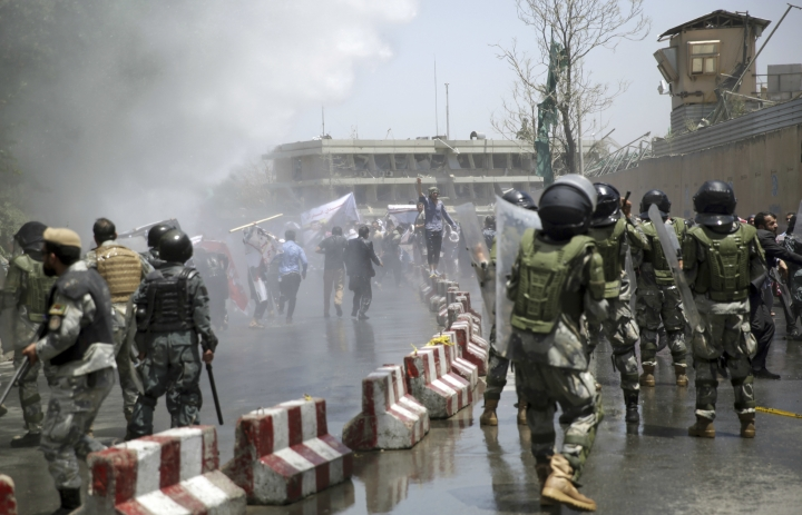 Police forces run as protesters throw stones during a demonstration in Kabul, Afghanistan, Friday, June 2, 2017. Hundreds of demonstrators demanded better security in the Afghan capital in the wake of a powerful truck bomb attack that killed scores of people. (AP Photo/Massoud Hossaini)