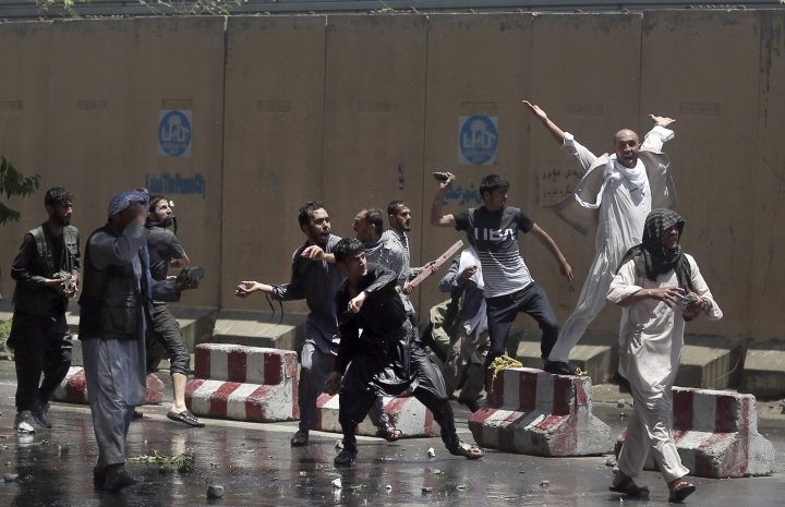 Protesters throw stones toward security forces in Kabul, Afghanistan, Friday, Jun 2, 2017. Some 500 people are demonstrating in Kabul for better security in the Afghan capital in the wake of a powerful truck bomb attack that killed 90 people. (AP Photos/Massoud Hossaini)