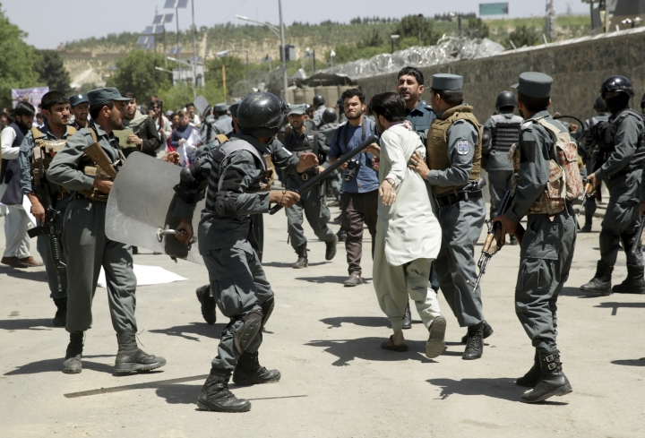 Policemen arrest a protester during a demonstration in Kabul, Afghanistan, Friday, Jun 2, 2017. Hundreds of demonstrators demanded better security in the Afghan capital in the wake of a powerful truck bomb attack that killed scores of people. (AP Photos/Massoud Hossaini)