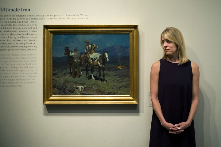 "In this Friday, June 2, 2017 photo, chief curator Amy Scott pauses for photos with a painting titled ""First Streak of Dawn"" by Frank Tenney Johnson at the Autry Museum of the American West, in Los Angeles. With Western American art long dismissed as unworthy of the fine art world, few collectors would have even cared 25 years ago if an early 20th century oil painting of cowboys or Indians on the frontier was authentic or not. Now, the owner of galleries in New Mexico and New York City is suing one of the world's largest Western American art auctions, a Nevada gallery and others for defamation, accusing them of falsely claiming a $1 million painting he sold by Tenney Johnson is a fake. ""It wasn't really until the late 1980s or mid- to early-1990s that a lot of art historians and museums began to start taking Western American art seriously,"" said Scott. (AP Photo/Jae C. Hong)"