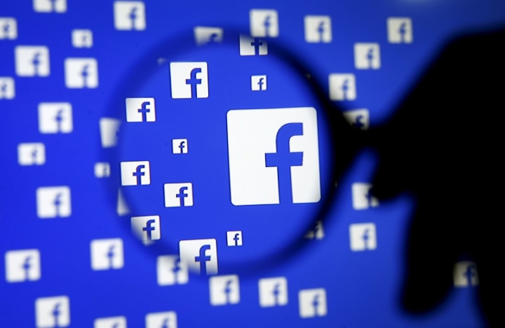 FILE PHOTO: A man poses with a magnifier in front of a Facebook logo on display December 16, 2015.   REUTERS/Dado Ruvic/Illustration/File Photo