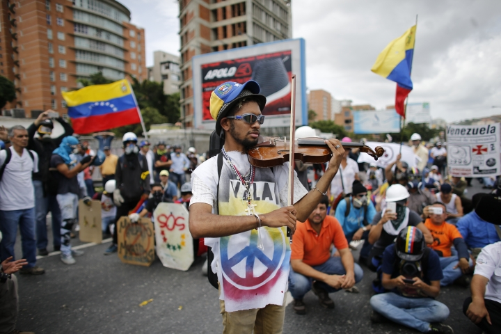 """FILE - In this May 31, 2017 file photo, Wuilly Arteaga plays his violin during an anti-government march in Caracas, Venezuela. """"When I play for the national guard, some of them listen to me, some of them cry. And when I play for the protesters, it gives them motivation to keep going,"""" Arteaga said. (AP Photo/Ariana Cubillos, File)"""