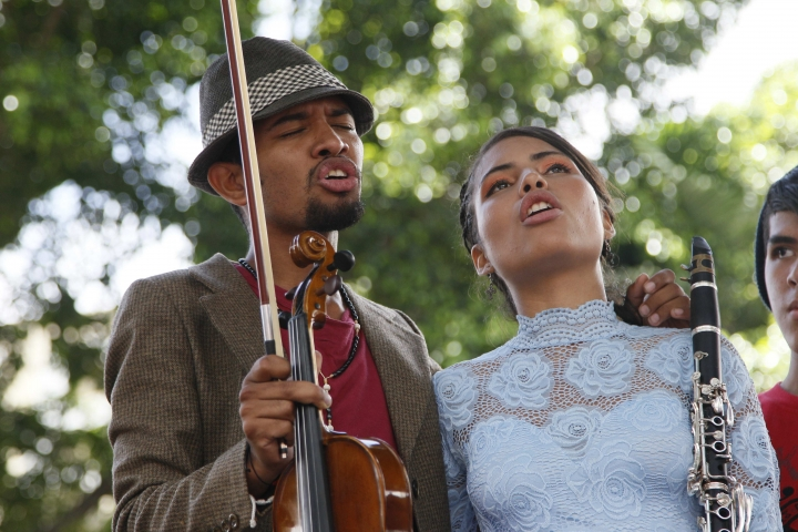 Violinist Wuilly Arteaga, left, sings with a fellow musician as they give a free concert in Caracas, Venezuela, Sunday, June 4, 2017. Arteaga, 23, has become a symbol of a more peaceful form of protest largely squashed out in almost daily clashes between rock-throwing youth and heavy-handed security forces that have left at least 65 dead and more than 1,100 injured. (AP Photo/Ariana Cubillos)