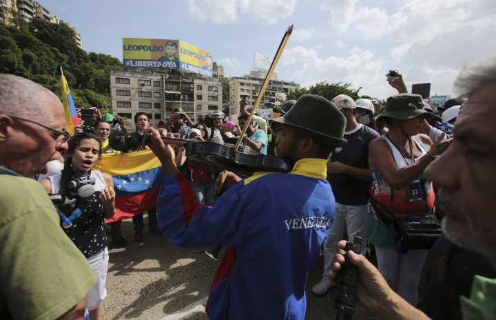 """In this May 27, 2017 photo, Wuilly Arteaga plays his violin during an anti-government protest in Caracas, Venezuela. """"I know my music creates a climate of peace, which is why I'll continue playing on the streets of Venezuela,"""" said Arteaga. (AP Photo/Fernando Llano)"""