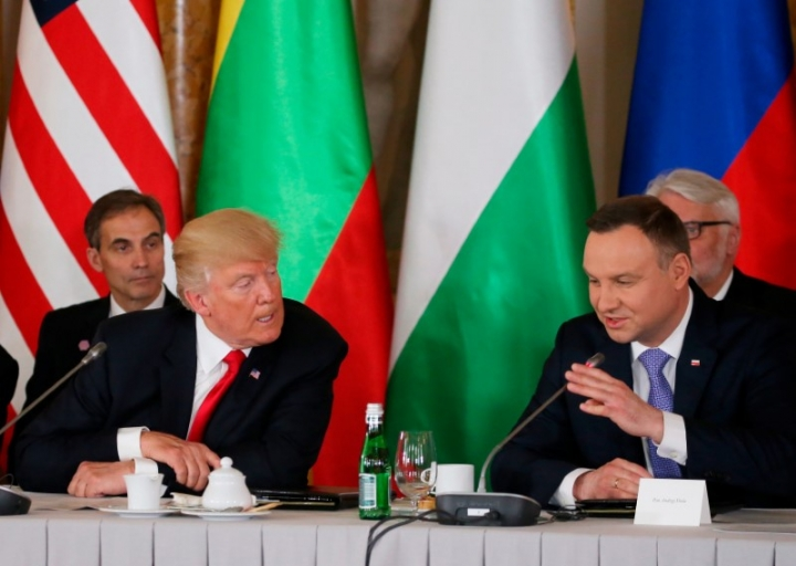 U.S. President Donald Trump talks to Polish President Andrzej Duda as U.S. ambassador to Poland Paul W. Jones looks on during the Three Seas Initiative Summit in Warsaw, Poland July 6, 2017. REUTERS/Carlos Barria