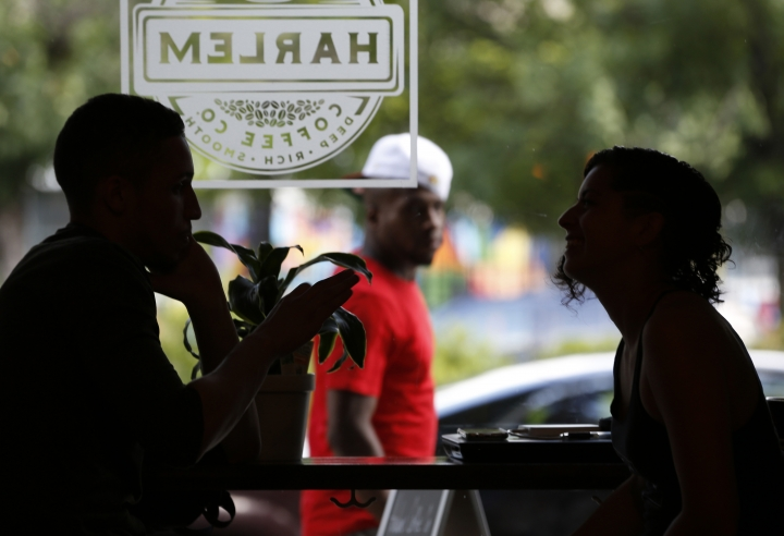 A passerby glances in the window as friends chat at Harlem Coffee Company, a six-month-old business located on Malcolm X Boulevard in southern Harlem, Monday, June 26, 2017, in New York. Some local realtors, business owners and restaurants have renamed the neighborhood SoHa, as in southern Harlem, but longtime residents are upset about the name change, which they feel demeans the area's rich politcal and cultural history. (AP Photo/Kathy Willens)