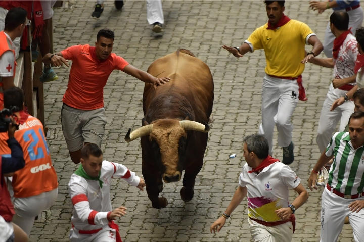 Revellers run in front of a Puerto de San Lorenzo fighting bull during the third running of the bulls at the San Fermin Festival, in Pamplona, northern Spain, Sunday, July 9, 2017. Revellers from around the world flock to Pamplona every year to take part in the eight days of the running of the bulls. (AP Photo/Alvaro Barrientos)