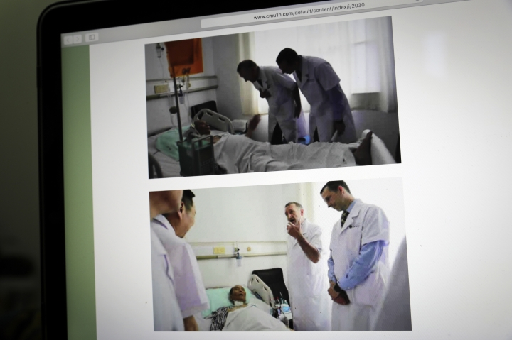 This image displayed on a screen in Beijing, Sunday, July 9, 2017, shows photos in the official website of the First Hospital of China Medical University in Shenyang, northern China, showing German Dr. Markus W. Buchler, left in top photo, and second right in bottom photo, of Heidelberg University, and American Dr. Joseph Herman, right in both top and bottom photos, of the MD Anderson Cancer Center at the University of Texas, meeting with China's Nobel Peace Prize laureate Liu Xiaobo at the hospital. The two foreign specialists who visited Liu on Saturday said Sunday that the cancer-stricken Liu is still able to travel abroad for treatment, apparently contradicting statements by Chinese experts who say a medical evacuation would be unsafe. (AP Photo/Andy Wong)