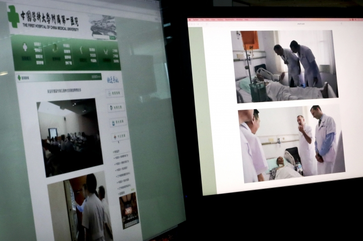 CORRECTS POSITIONS - These images displayed on the screens in Beijing, Sunday, July 9, 2017, show the official website of the First Hospital of China Medical University in Shenyang, northern China, and photos showing German Dr. Markus W. Buchler, left in top photo, and second right in bottom photo, of Heidelberg University, and American Dr. Joseph Herman, right in both top and bottom photos, of the MD ­Anderson Cancer Center at the University of Texas, meeting with China's Nobel Peace Prize laureate Liu Xiaobo at the hostpital. The American and German specialists who visited Liu over the weekend said Sunday that cancer-stricken Liu is still able to travel abroad for treatment, apparently contradicting statements by Chinese experts who maintain that a medical evacuation would be unsafe. (AP Photo/Andy Wong)