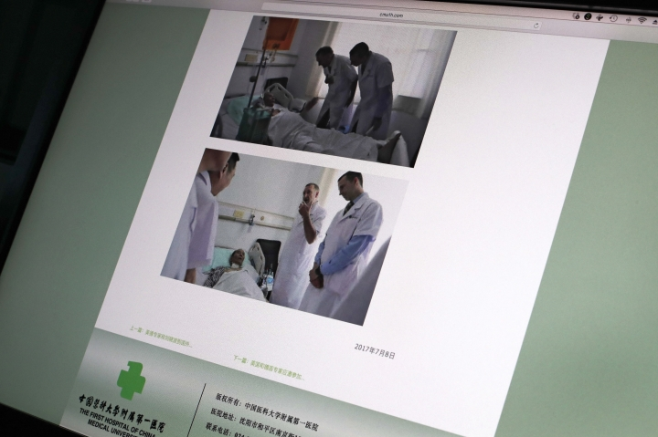 CORRECTS POSITIONS - This image displayed on a screen in Beijing, Sunday, July 9, 2017, shows photos in the official website of the First Hospital of China Medical University in Shenyang, northern China, showing German Dr. Markus W. Buchler, left in top photo, and second right in bottom photo, of Heidelberg University, and American Dr. Joseph Herman, right in both top and bottom photo, of the MD ­Anderson Cancer Center at the University of Texas, meeting with China's Nobel Peace Prize laureate Liu Xiaobo at the hostpital. The American and German specialists who visited Liu over the weekend said Sunday that cancer-stricken Liu is still able to travel abroad for treatment, apparently contradicting statements by Chinese experts who maintain that a medical evacuation would be unsafe. (AP Photo/Andy Wong)