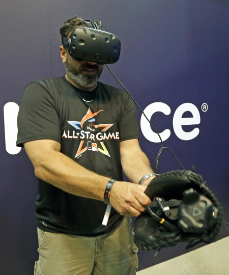 In this Friday, July 7, 2017, photo, Andy Grabin takes off the catcher mitt with sensors after catching visual pitches at the All-Star FanFest in Miami Beach, Fla. Virtual Reality baseball is a hit at the All-Star FanFest in Miami. Fans get to feel what it's like to be the San Francisco Giants' Buster Posey catching without the pain of snatching major league pitches at 86-to-93 mph. (AP Photo/Alan Diaz)