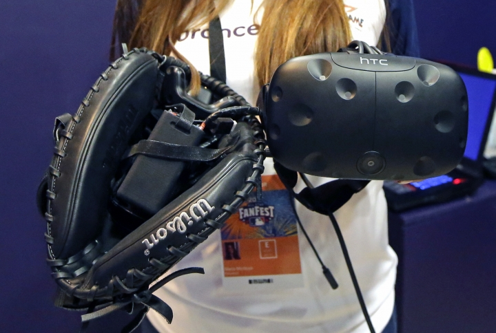 In this Friday, July 7, 2017, photo, the catcher mitt with sensors and goggles used for virtual catching are shown at the All-Star FanFest in Miami Beach, Fla. Fans put on goggles and a catcher's mitt, crouch and get ready. They will never catch a 104 mph from Aroldis Chapman. But at the All-Star FanFest they could feel like what it is like to be Buster Posey, receiving virtual pitches. (AP Photo/Alan Diaz)