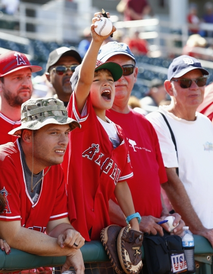 FILE - In this March 8, 2017, file photo, a Los Angeles Angels fan shouts for Mike Trout to sign his baseball, which he did, prior to a spring training baseball game against the Cincinnati Reds, in Goodyear, Ariz. Bryce Harper, Mike Trout and Aaron Judge have become the face of baseball as a gleaming, modernist ballpark and a city known for its Latino culture host the All-Star Game for the first time. (AP Photo/Ross D. Franklin, File)