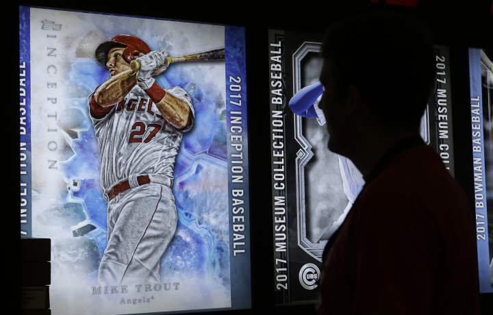In this Friday, July 7, 2017, photo, a fan looks at an enlarged baseball card of Los Angeles Angels' Mike Trout, at a booth at the All-Star FanFest at the Miami Beach Convention Center in Miami Beach, Fla. Virtual Reality baseball is a hit at the All-Star FanFest in Miami. Fans get to feel what it's like to be the San Francisco Giants' Buster Posey catching without the pain of snatching major league pitches at 86-to-93 mph. (AP Photo/Alan Diaz)