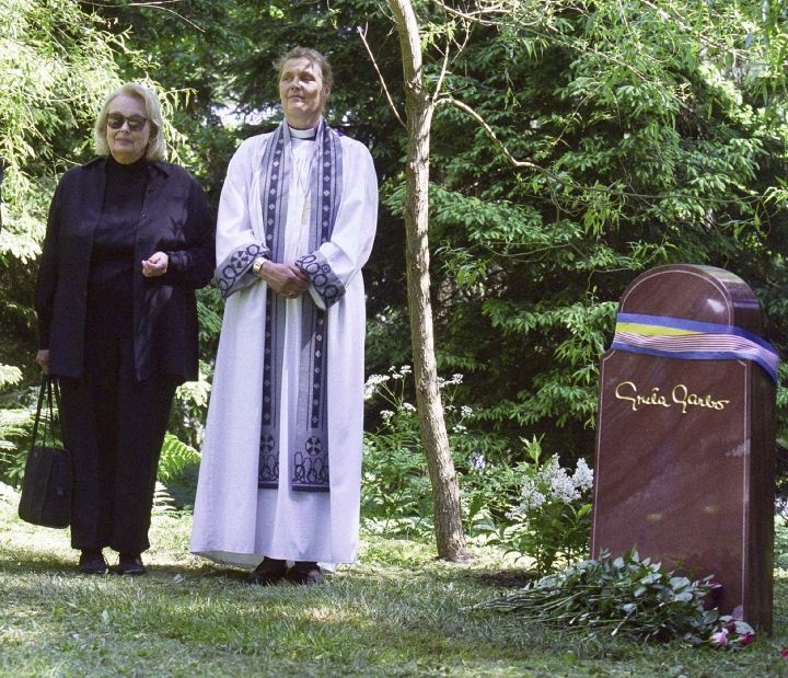 FILE - In this June 17, 1999 file photo, Gray Gustafson Reisfield, left, and Bishop Caroline Krook stand next to the tombstone of Greta Garbo after the memorial service at the Woodland Cemetery in Stockholm, Sweden. Reisfield, the sole heiress to her aunt Greta Garbo's estate and a woman who was a long-time companion to the late Swedish-born actress, has died, a family member said Monday, July 10, 2017. (Tobias Rostlund/TT via AP, File)