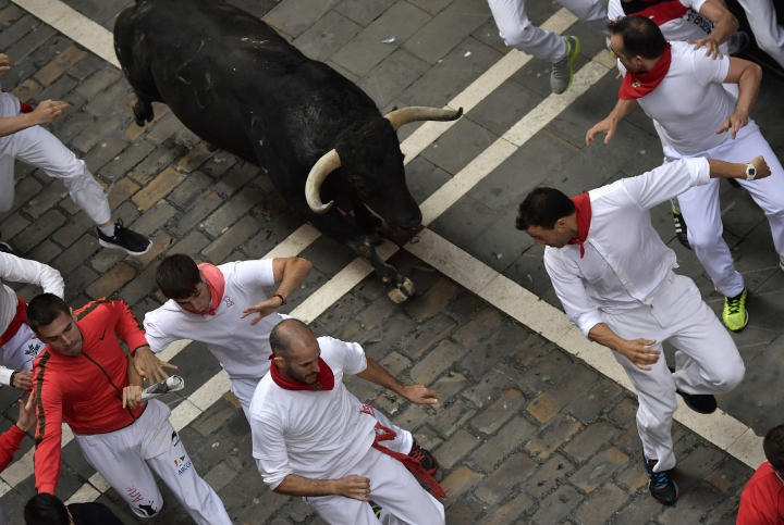 Revellers run in front of Jandilla's fighting bulls during the running of the bulls at the San Fermin Festival, in Pamplona, northern Spain, Tuesday, July 11, 2017. Revellers from around the world flock to Pamplona every year to take part in the eight days of the running of the bulls. (AP Photo/Alvaro Barrientos)