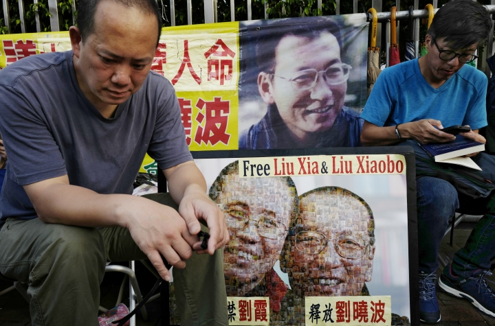 Protesters display portraits of jailed Chinese Nobel Peace laureate Liu Xiaobo during a demonstration outside the Chinese liaison office in Hong Kong, Wednesday, July 12, 2017. Liu is in life-threatening condition with multiple organ failure and his family has opted against inserting a breathing tube needed to keep him alive, the hospital treating him said Wednesday. (AP Photo/Vincent Yu)