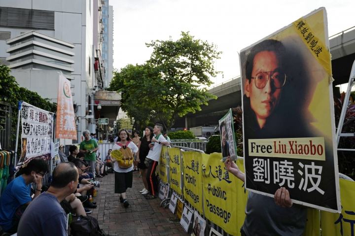 Protesters display portrait of jailed Chinese Nobel Peace laureate Liu Xiaobo during a demonstration outside the Chinese liaison office in Hong Kong, Wednesday, July 12, 2017. Liu is in life-threatening condition with multiple organ failure and his family has opted against inserting a breathing tube needed to keep him alive, the hospital treating him said Wednesday. (AP Photo/Vincent Yu)