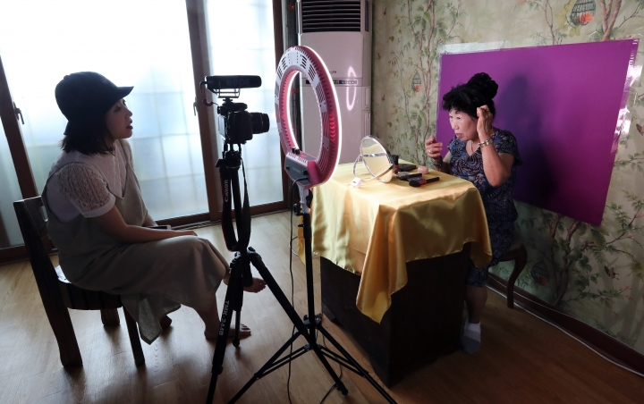 In this July 11, 2017 photo, South Korea's YouTube star, Park Makrye, 70, right, and her granddaughter Kim Yura, 27, left, give a demonstration of make-up tutorials for Park's YouTube channel during an interview at her home in Yongin, South Korea. Park's videos are all about showing off her wrinkles and her elderly life in the raw. Young South Koreans find her so funny and adorable that big companies like Samsung Electronics and Lotte are banking on her popularity. But despite her new life as a celebrity, she still gets up before dawn to run her diner. (AP Photo/Lee Jin-man)