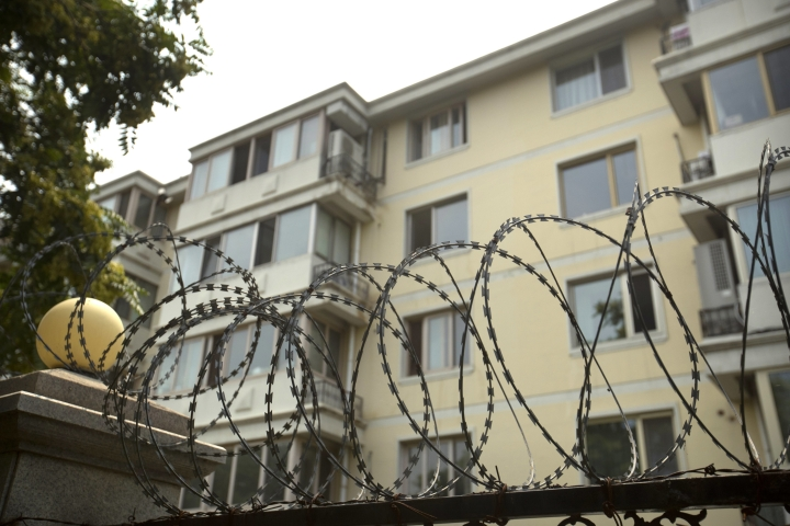 """Coils of barbed wire top a fence next to an apartment building where Liu Xia, the wife of Chinese dissident and Nobel Prize winner Liu Xiaobo, had been living under house arrest in Beijing, Friday, July 14, 2017. Imprisoned for all the seven years since he was awarded the Nobel Peace Prize, Liu Xiaobo never renounced the pursuit of human rights in China, insisting on living a life of """"honesty, responsibility and dignity."""" China's most prominent political prisoner died Thursday of liver cancer at 61. (AP Photo/Mark Schiefelbein)"""