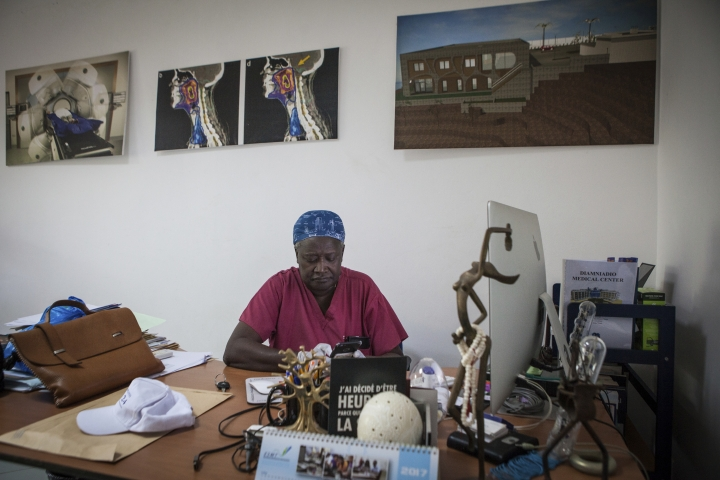 Dr. Abdoul Aziz Kasse sits at his desk at the Clinique des Mamelles in Dakar, Senegal, Thursday, July 13, 2017. The word cancer is rarely spoken in Senegal, synonymous with death in a country where many are only diagnosed in the later stages of disease and radiation therapy can be difficult to access. Cancer has become an emerging public health problem in West Africa, and the lack of strong prevention, good screening and treatment often leaves outcomes grim. (AP Photo/Jane Hahn)