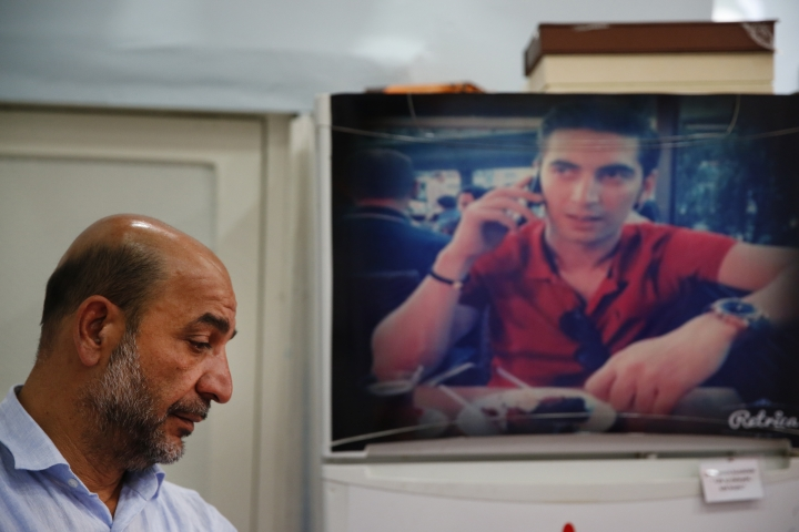 In this Thursday, July 6, 2017 photo, Tarkan Ecebalin, left, stands next to a picture of his late son Tolga, at their former home in Istanbul. The father turned the modest house into a museum honouring his child, who was 27 when he was killed during the July 15, 2016 failed military coup. (AP Photo/Lefteris Pitarakis)