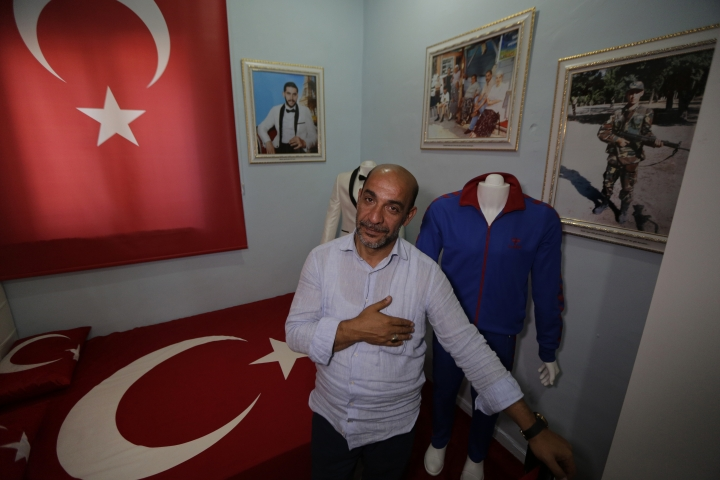 In this Thursday, July 6, 2017 photo, Tarkan Ecebalin stands in his late son Tolga's bedroom where Tolga's bed is now draped with a Turkish flag. The father turned their former home into a museum honouring his child, who was 27 when he was killed during the July 15, 2016 failed military coup. (AP Photo/Lefteris Pitarakis)